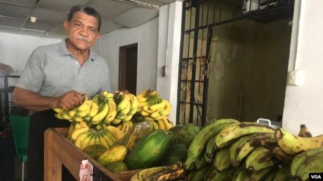 José Pulgar, ayuda a vender productos, frutas y verduras en un mercado de Maracaibo, donde los clientes generalmente pagan en dólares.