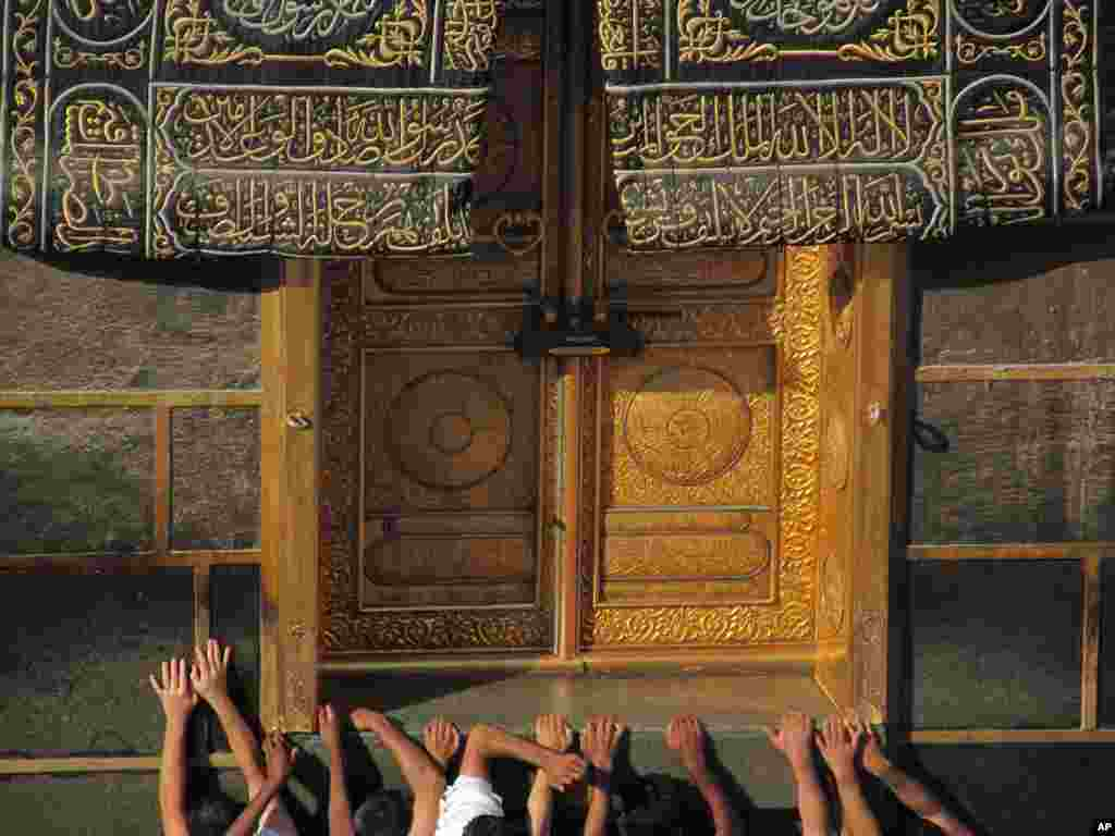 Muslim pilgrims pray at the door of the Kabaa in the holy city of Mecca, Saudi Arabia, Oct. 13, 2013.
