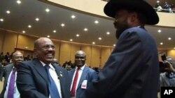 Presiden Sudan Omar al-Bashir (kiri) dan Presiden Sudan Selatan Salva Kiir bersalaman saat bertemu di Addis Ababa, Ethiopia, Minggu (15/7).