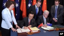 Australian Prime Minister Tony Abbott, back center, watches as China's Minister of Commerce Gao Hucheng, second left, and Australian Minister for Trade Andrew Robb, second right, sign a free trade agreement between the two countries in Canberra, Australia