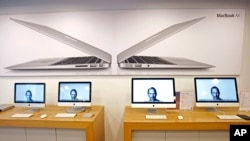 Portraits of the late Steve Jobs illuminate Computer monitors in an Apple retail store in Taiwan, Oct. 6, 2011. (AP)
