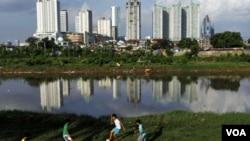 Anak-anak Indonesia bermain bola di pinggir sebuah sungai di Jakarta. Pemerintah Indonesia diharapkan bisa mewujudkan pertumbuhan ekonomi untuk menciptakan kesejahteraan.