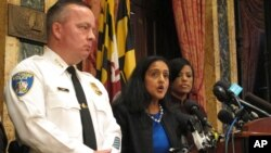 Vanita Gupta, head of the Justice Department's Civil Rights Division, discusses the department's findings on the investigation into the Baltimore City Police Department as Police Commissioner Kevin Davis, left, and Mayor Stephanie Rawlings-Blake, right, listen at City Hall in Baltimore, Aug. 10, 2016.