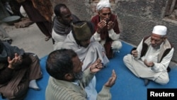 Neighbors pray outside the residence of 62-year-old heart patient Chaudhry Mohammad Gulab after he was buried in Lahore on January 27, 2012. Gulab's health started to deteriorate after he was prescribed a new medication, his younger brother said.