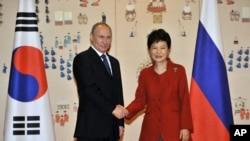 "Presiden Korea Selatan Park Geun-hye berjabat tangan dengan Presiden Rusia Vladimir Putin (kiri) di Kantor Kepresidenan ""Gedung Biru"" di Seoul, Korea Selatan (13/11)."