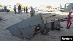People stand next to the wreckage of a government MiG Libyan fighter jet that crashed during fighting Islamist fighters, in Benghazi, July 29, 2014.