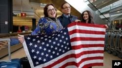 Jayne Novak, izquierda, junto a su esposo, Allen Novak, tras llegar de Irán, y su hija Nikta, posan con una bandera estadounidense en el aeropuerto internacional de Seattle, Washington, el lunes, 6 de febrero, de 2017.