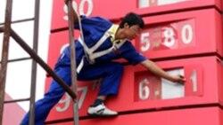 2009年7月29日: 工人在湖北省宜昌市加油站调整属于国营企业的中石化燃油价格标牌