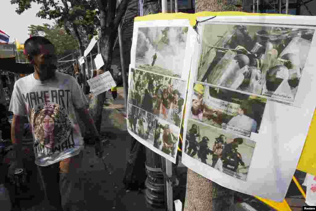 Một người biểu tình chống chính phủ xem các bức ảnh chụp trong vụ đụng độ với cảnh sát trong cuộc biểu tình bên ngoài Tòa nhà Chính phủ ở Bangkok, Thái Lan, 29/12/13