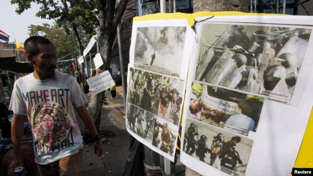 An anti-government protester walks past pictures taken during clashes with riot policemen, during a rally outside the Government House in Bangkok December 29, 2013.