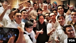 "Para relawan ""Kita Satu"" berfoto bersama Erick Thohir pada acara di Jakarta, Kamis (13/12). (Foto: VOA/Ahmad Bhagaskoro)"