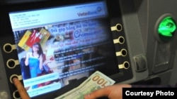 A customer uses a VietinBank cash machine to do a currency exchange transaction. (VietinBank)