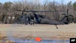 FILE - A National Guard helicopter picks up water from a small pond near Hutchinson, Kansas, March 7, 2017. Fires raged in parts of Kansas, Oklahoma, Texas and Colorado.