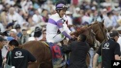 """El jockey Mario Gutierrez celebra tras ganar el Derby de Kentucky con el potro """"I'll Have Another"""", extendiendo los festejos del 5 de mayo de los mexicanos."""