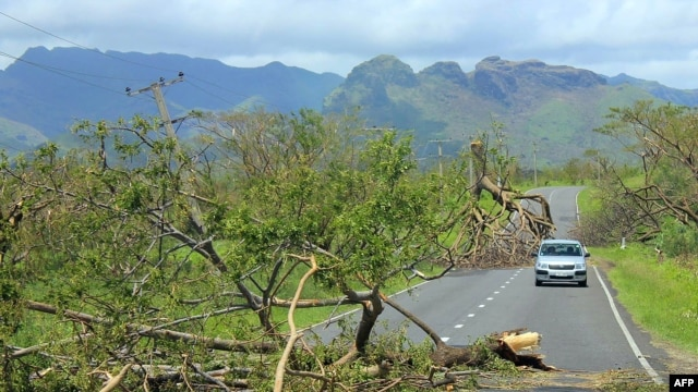 This undated handout photograph released on Feb. 22, 2016, by the Fiji government shows a car driving past uprooted trees following Cyclone Winston in Fiji's western division.
