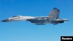 日本防卫省2014年3月24日公布的照片显示中国苏-27战机飞越东中国海上空。