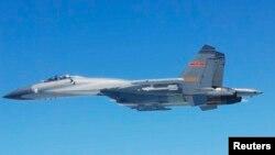 日本國防部5月25日公佈的圖片顯示﹐一架中國SU-27戰機於24日在東中國海上空飛行。
