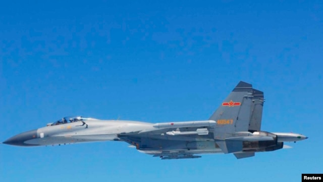 A Chinese SU-27 fighter flies over the East China Sea, in this handout photo taken May 24, 2014 and released by the Defense Ministry of Japan, May 25, 2014.