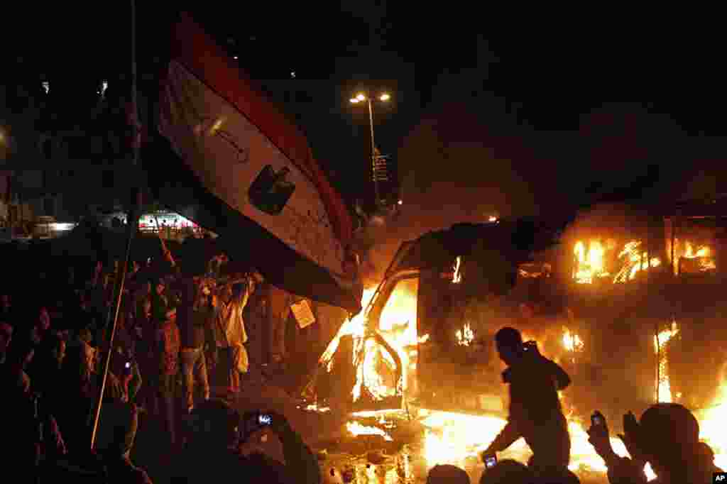 Protesters use camera phones to capture a burning state security armored vehicle that demonstrators commandeered, brought to Tahrir Square and set alight, Cairo, Egypt, January 28, 2013.
