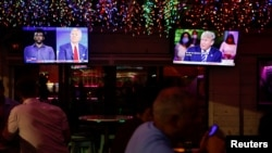 The dual town halls of U.S. Democratic presidential candidate Joe Biden and U.S. President Donald Trump, who are both running in the 2020 U.S. presidential election, are seen on television monitors at Luv Child restaurant ahead of the election in Tampa, Florida.