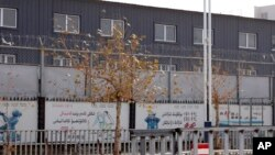 新疆和田市服装就业培训基地的外墙被两层铁丝网围住。(2018年12月5日)
