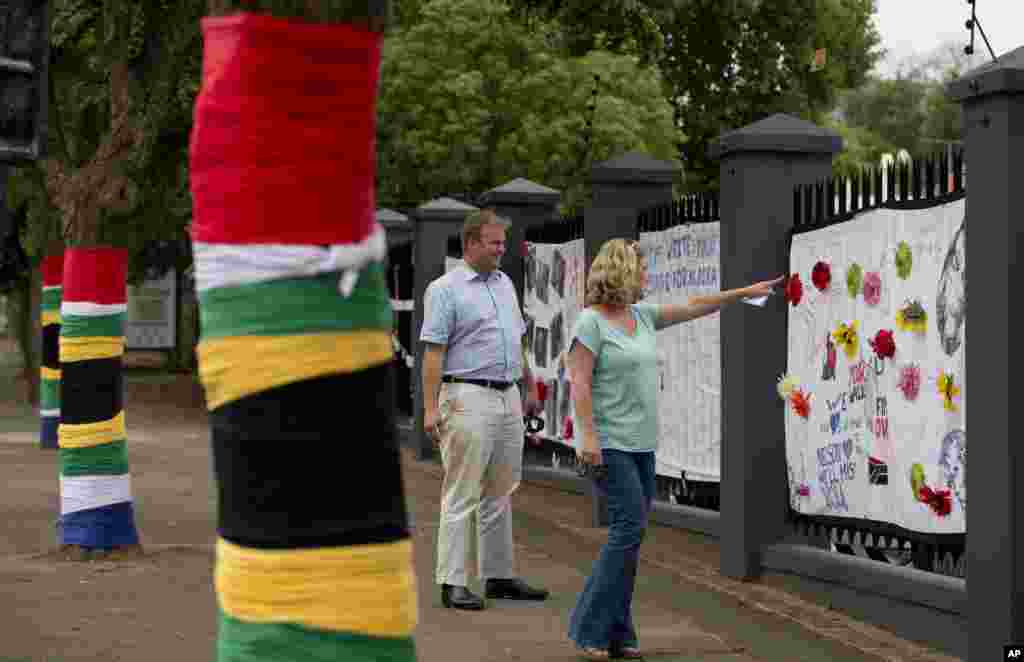 People leave messages for Nelson Mandela on a memorial site adorned with South African flags on trees, in Rosebank, an affluent district of Johannesburg, Dec. 9, 2013.