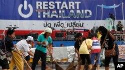 Para relawan membersihkan lokasi yang digunakan sebagai pusat protes anti-pemerintah Thailand di Bangkok (5/2).