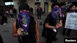 Para perempuan peserta unjuk rasa menentang kekerasan gender memegang pisau mainan di Santiago, Chile, 11 Meil 2018.
