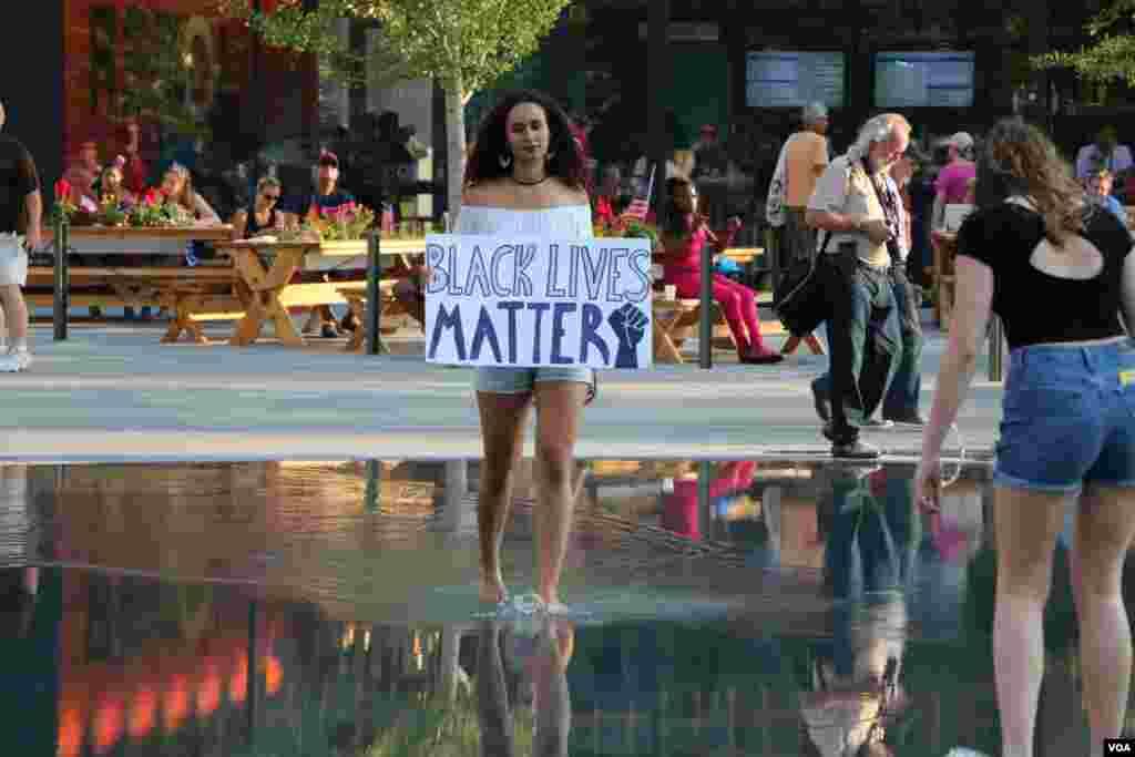 این دختر از جنبش «جان سیاهان مهم است»، در حوضچه وسط شهر توجه ها را به خود جلب می کند.