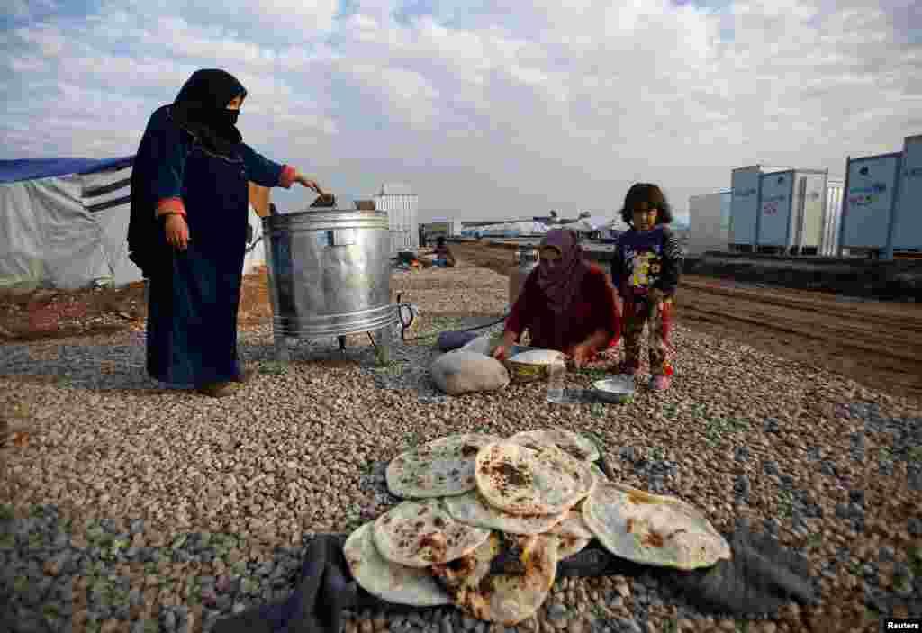زنان آواره در یک اردوگاه در نزدیکی موصل عراق نان میپزند.