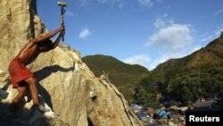 Seorang penambang memecahkan batu yang mengandung emas di Poboya, Sulawesi Tengah. (Reuters/Yusuf Ahmad)