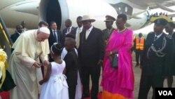 Paus Fransiskus disambut oleh anak-anak Uganda saat mendarat dari pesawat di kota Entebbe, Jumat (27/11).