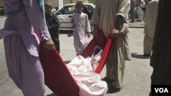 Warga Afghanistan mengangkut jenazah seorang perempuan yang menjadi korban ledakan bom di Herat (18/8).