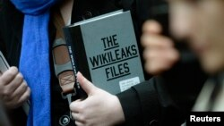 FILE - A supporter of WikiLeaks founder julian Assange holds a copy of The WikiLeaks Files outside the Ecuadorian embassy in central London, Britain Feb. 5, 2016.