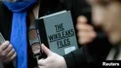 维基解密创始人阿桑奇的一位支持者在厄瓜多尔驻伦敦大使馆外手举一本维基解密档案(2016年2月5日)