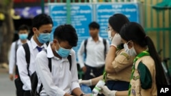Students disinfect their hands to avoid the contact of coronavirus before their morning class at Santhormok high school, in Phnom Penh, Cambodia, Monday, Nov. 2, 2020. (AP Photo/Heng Sinith)