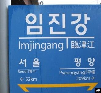 Binh sĩ Nam Triều Tiên đi ngang qua bảng chỉ đường cho thấy khoảng cách từ ga Imjingang đến Bình Nhưỡng, ngày 12/6/2013.