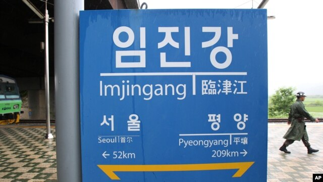 A South Korean army soldier walks near a sign showing the distance to the North Korean capital Pyongyang and to South's capital Seoul from Imjingang Station near the border village of Panmunjom in Paju, South Korea, June 12, 2013.