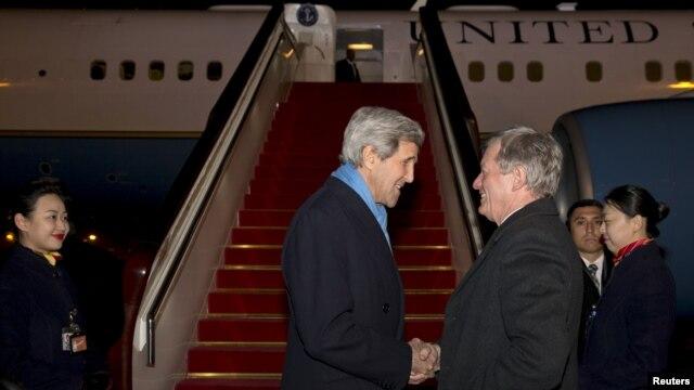 Госсекретаря Джона Керри в Пекине встречает посол США в Китае Макс Бокус. 26 января, 2016