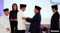Capres 01 Joko Widodo (kiri) berjabat tangan dengan Capres 02 Prabowo Subianto sementara Cawapres 01 Ma'ruf Amin dan Cawapres 02 Sandiaga Uno menyaksikan usai debat pertama di Jakarta, Kamis malam (17/1).