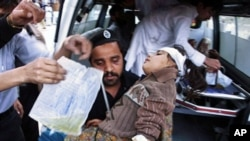 A Pakistani man lifts a girl injured in a suicide attack from an ambulance to be treated at a hospital in Peshawar, 05 Mar 2010