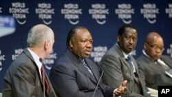 Gabon President Ali Bongo Ondimba (2L) sits between UN special rapportuer David Nabarro (L) and Kenyan PM Raila Odinga (2R) during the second day of the World Economic Forum on Africa in Cape Town on May 5, 2011