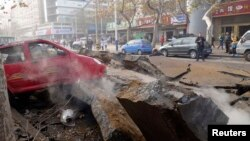 A man is trapped in the rubble of a damaged road after an explosion at a Sinopec Corp oil pipeline in Huangdao, Qingdao, Shandong Province, Nov. 22, 2013.