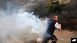 Seorang pendukung Mohamed Morsi berlari dari kejaran tentara Mesir di Kairo (14/8).