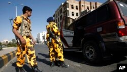 Houthi Shiite Yemenis wearing police uniforms check a vehicle at a street ahead of a tribal meeting held by Houthi Shiite rebels in Sanaa, Yemen, Oct. 31, 2014.