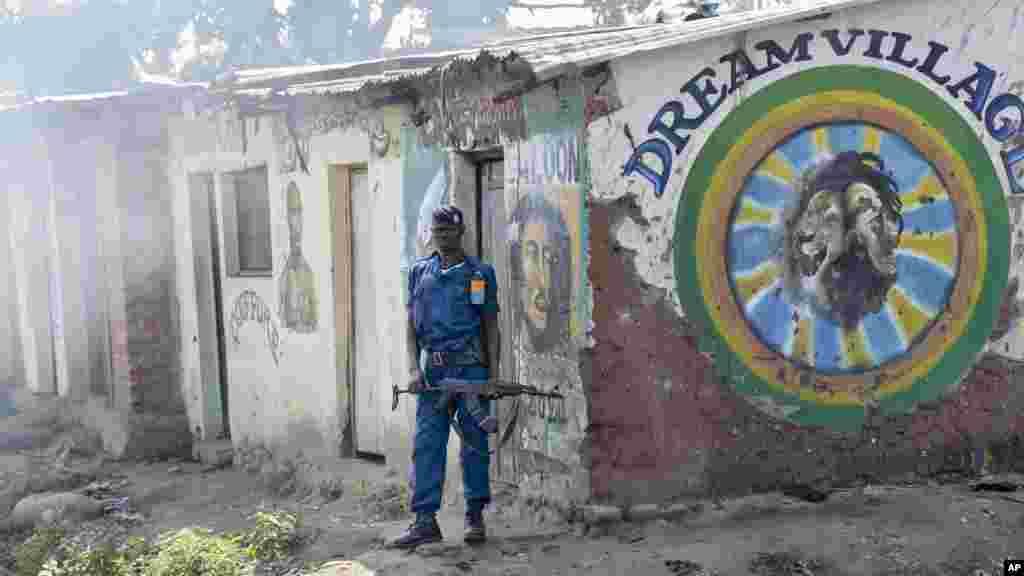 """Um policial do Burundi guardando posto à porta da barbearia """"Dream Village"""". A fumaça que se aproxima dele é de gás lacrimogéneo, (esquerda) durante os confrontos entre manifestantes da oposição e forças de segurança no distrito de Cibitoke da capital Bujumbura, Burundi, 29 de Maio, 2015."""