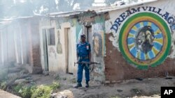 Un policier embusqué attend des manifestants alors que des grenades lacrymogènes ont été lancées, dans le district de Cibitoke, près de Bujumbura, le 29 mai 2015