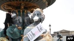 Seorang demonstran memakaikan masker pada patung-patung dalam unjuk rasa memprotes polusi udara di place de la Concorde di Paris, on 31 Maret 2018. / AFP PHOTO / JACQUES DEMARTHON