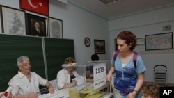 A Turkish woman prepares to cast her vote at a polling station in Ankara, Turkey, June 12, 2011