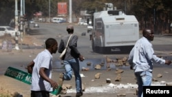 FILE - Opposition party supporters clash with police in Harare, Zimbabwe, Aug. 26, 2016.